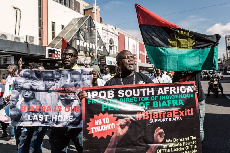 Protesters hold posters and a Biafra flag as they take part in a demonstration in Durban, South Africa, on May 30, 2019.