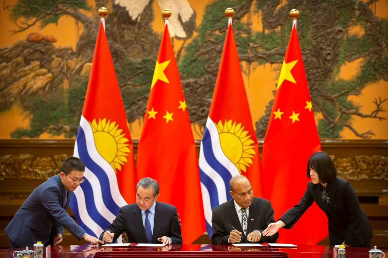 Chinese Foreign Minister Wang Yi and Kiribati President Taneti Maamau sign a memorandum of understanding at the Great Hall of the People in Beijing, on Jan. 6.