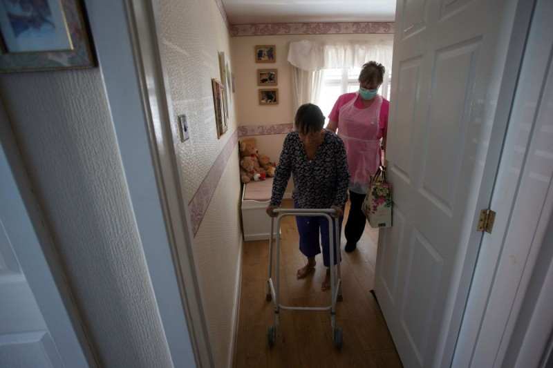 Dawn, a carer, tends to  her client, Tina, who has multiple sclerosis and is considered in the high-risk category during the COVID-19 pandemic, during a home visit in Scunthorpe, northern England, on May 8.