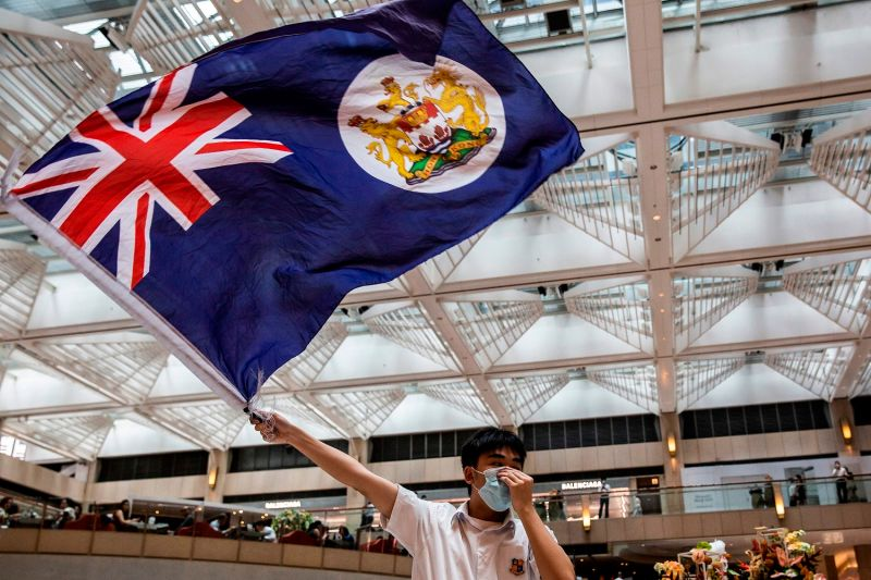 A pro-democracy protester waves a British colonial flag in Hong Kong