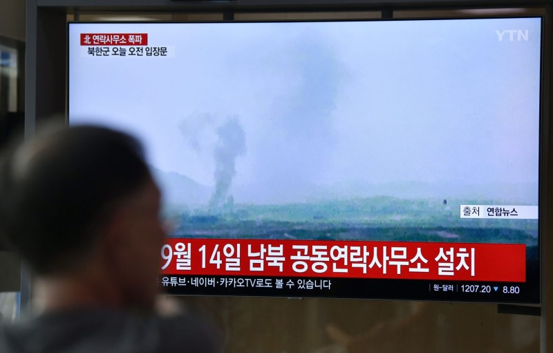 TOPSHOT - People watch a television news screen showing an explosion of an inter-Korean liaison office in North Korea's Kaesong Industrial Complex, at a railway station in Seoul on June 16, 2020.