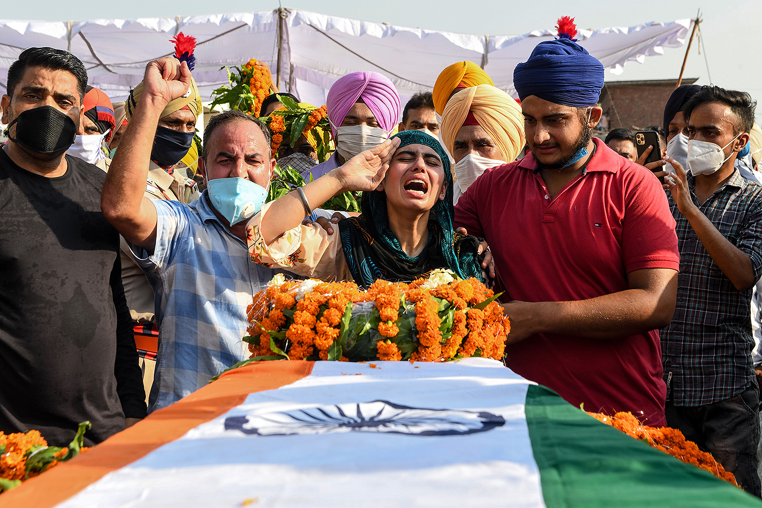 Sandeep Kaur (center) and her brother Prabhjot Singh (second from right) react after laying wreaths of flowers on the coffin of their father, Satnam Singh, a soldier who was killed in a recent clash with Chinese forces, during the cremation ceremony at Bhojraj village near Gurdaspur, India, on June 18. A bloody clash between troops on the disputed India-China border claimed at least 20 Indian soldiers' lives. NARINDER NANU/AFP via Getty Images
