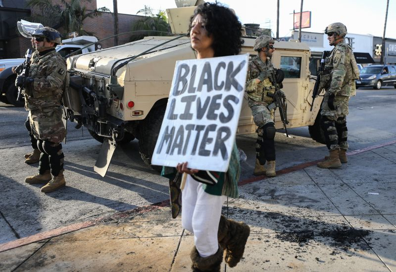 A woman carries a 'Black Lives Matter' sign past U.S. National Guard troops in the Fairfax District, an area damaged during yesterday's unrest, after the troops were activated by California Governor Gavin Newsom following violent demonstrations in response to George Floyd's death on May 31, 2020 in Los Angeles.
