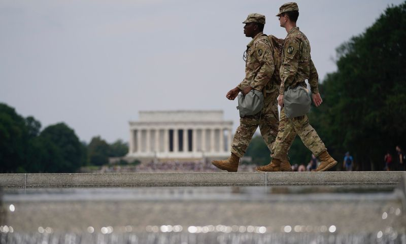 Two members of the National Guard walk past at the World War II Memorial as protests against police brutality and racism take place