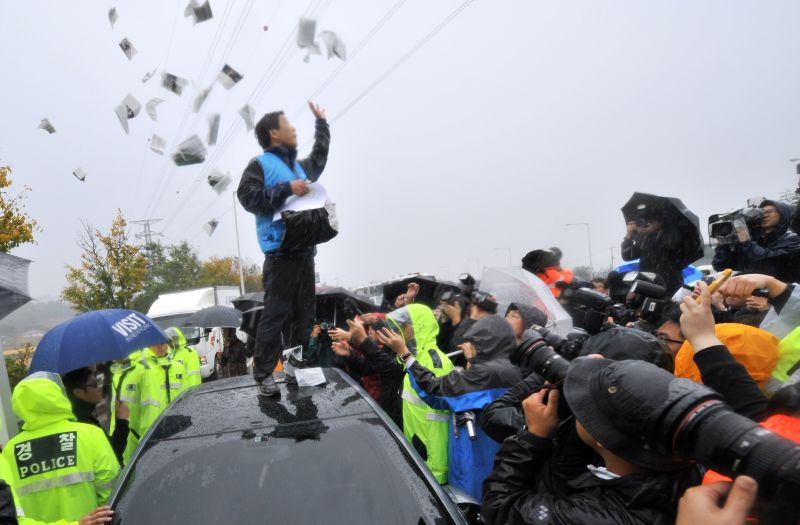 Park Sang-Hak, an activist and defector from North Korea, scatters anti-Pyongyang leaflets as police block his planned rally near the tense border on a roadway in Paju, north of Seoul, on Oct. 22, 2012.
