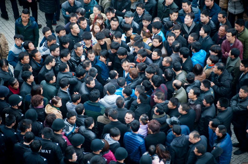 Workers gather on a square before the government headquarters in Wenling, in China's Zhejiang province, to protest after an extensive crackdown on workplace safety standards forced the closure of more than 4,500 shoe factories, on Feb. 17, 2014.