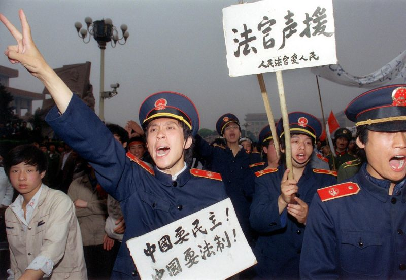 Beijing magistrates wearing court uniforms join workers demonstrating in support of student hunger-strikers gathered at Tiananmen Square, in Beijing on May 18, 1989.