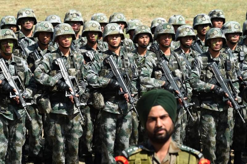 An Indian Army soldier stands in front of a group of People's Liberation Army soldiers after participating in a joint anti-terrorism drill on Nov. 25, 2016.