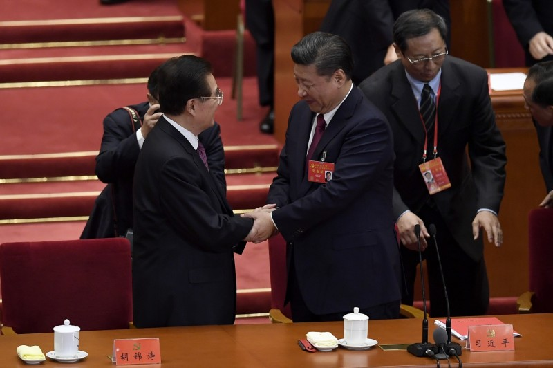 Chinese President Xi Jinping, right, shakes hands with China's former President Hu Jintao