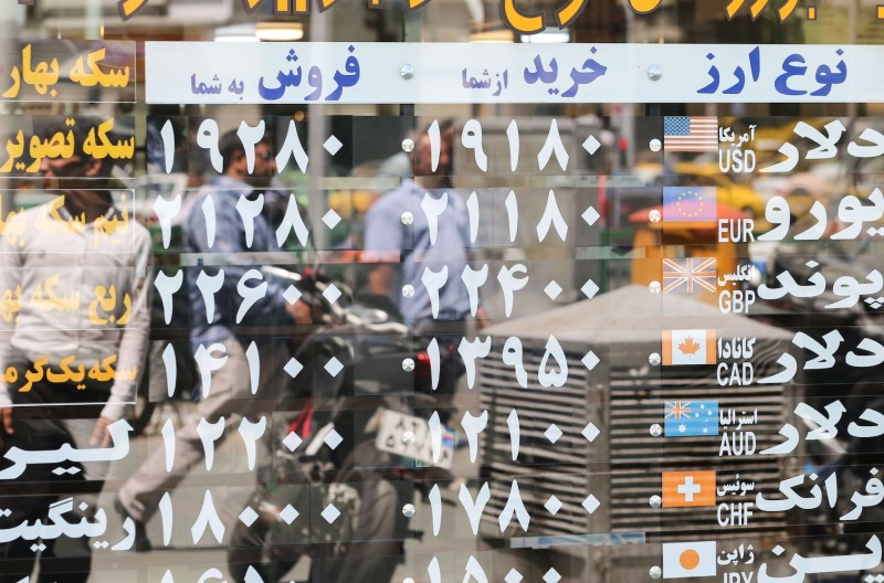 Pedestrians are reflected in a window displaying currency exchange rates in the Iranian capital Tehran on June 22.