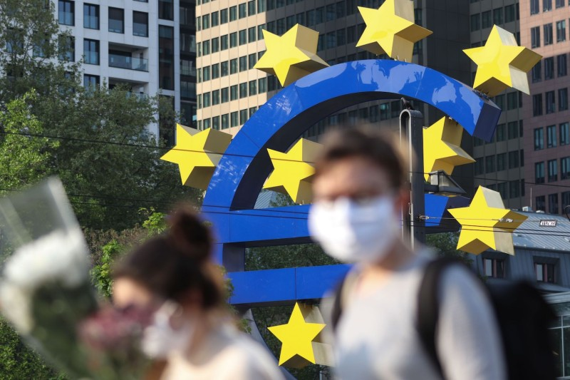 People wearing face masks walk in front of a euro sign in Frankfurt am Main, Germany, on April, 24.