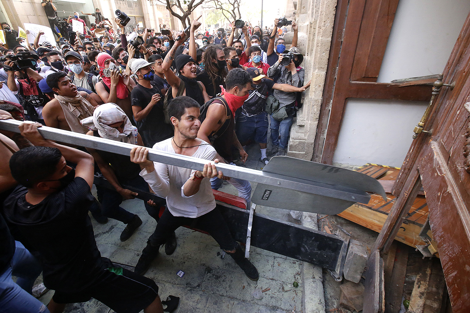 Demonstrators smash a door during a protest in Guadalajara, Mexico, on June 4 following the death of a young man while in police custody. ULISES RUIZ/AFP via Getty Images