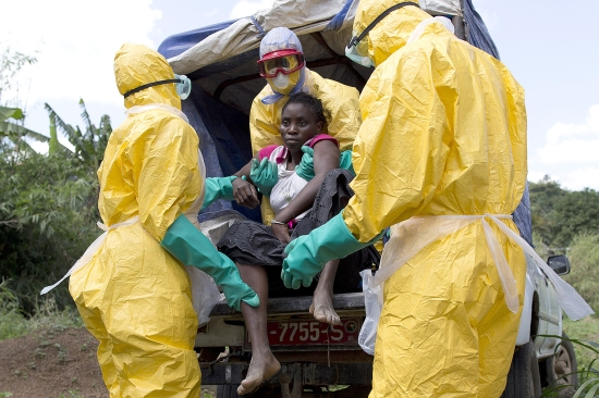 Health workers assist a patient suspected of having Ebola on their way to an Ebola treatment center run by the French Red Cross in Patrice near Macenta, Guinea, on Nov. 21, 2014.