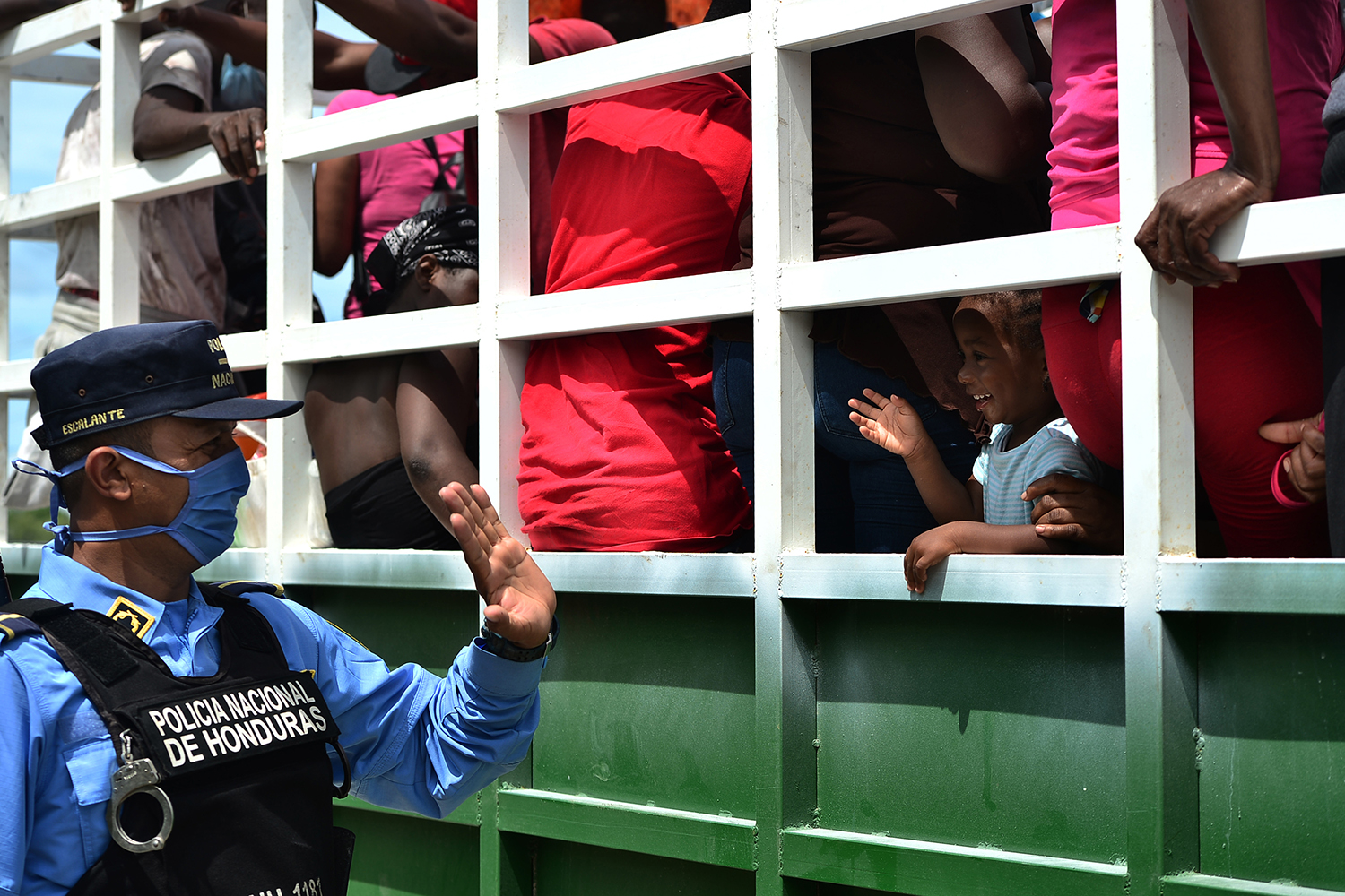 A police officer waves at a migrant girl riding in a caravan in Cerro de Hula, Honduras, on June 3. Nearly one hundred migrants from Congo, Ghana, Ivory Coast, Haiti, and Cuba heading from Honduras to Mexico were stopped by the police for sanitary controls amid the coronavirus pandemic. ORLANDO SIERRA/AFP via Getty Images