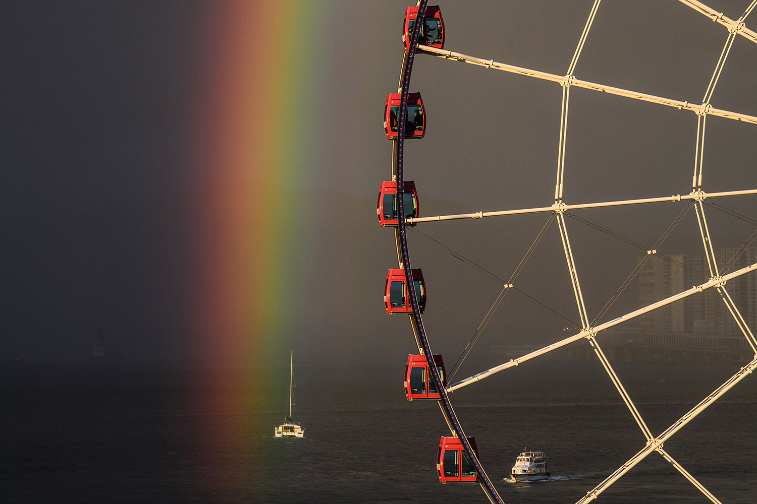 Passengers sit on a Ferris wheel in Hong Kong on June 16 as a rainbow appears after a rain shower during sunset. ANTHONY WALLACE/AFP via Getty Images