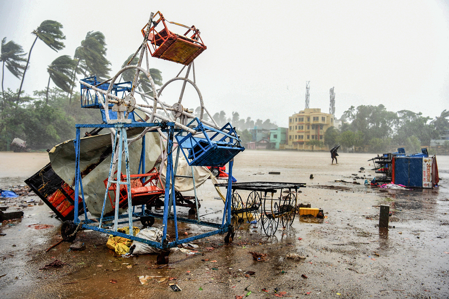 A man holding an umbrella walks past a small, damaged Ferris wheel in Alibag, India, in the Raigad District on June 3 following Cyclone Nisarga's landfall along India's western coast. STR/AFP via Getty Images