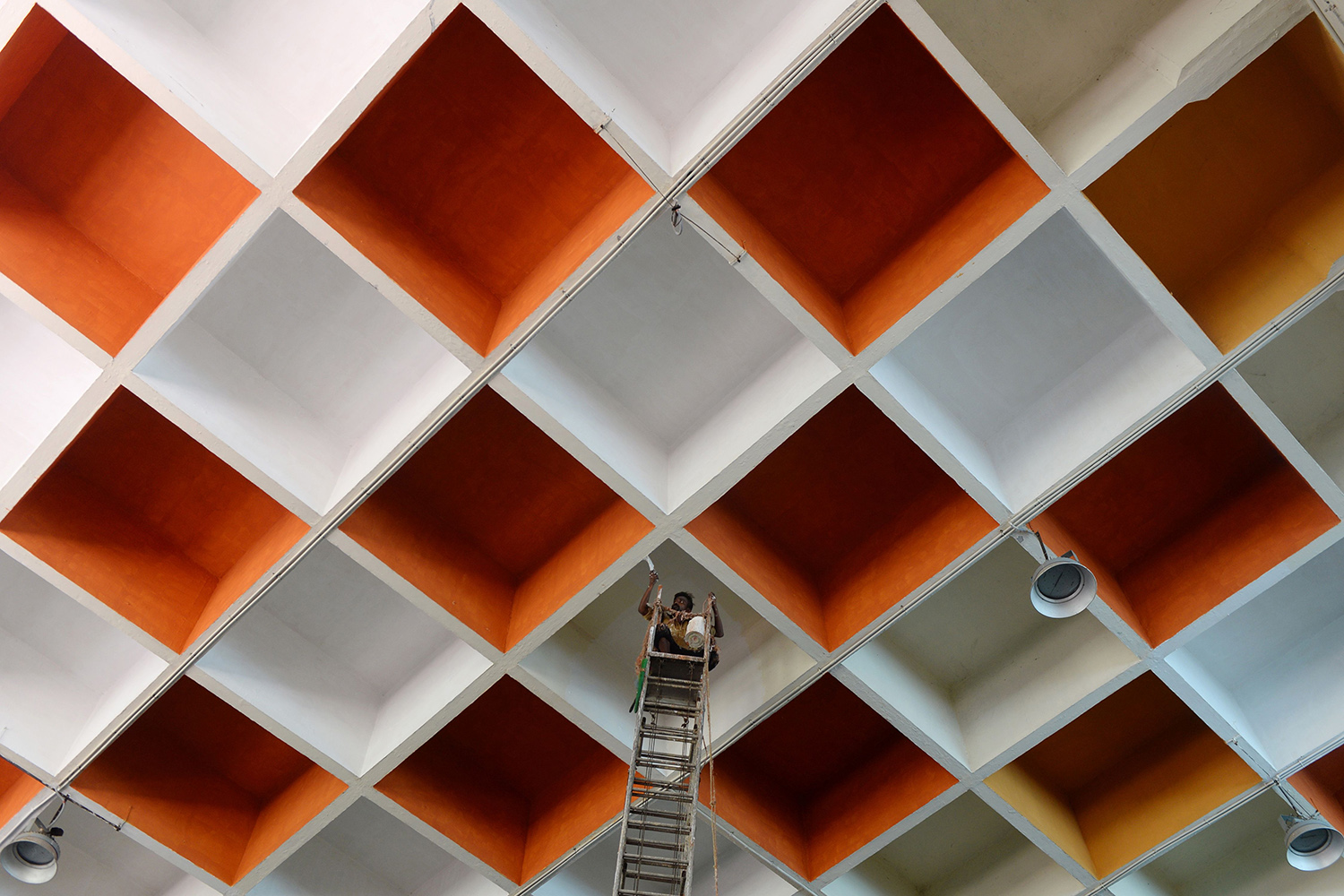 A worker paints the ceiling of a railway station in Chennai, India, on June 18 after the government eased a nationwide lockdown. ARUN SANKAR/AFP via Getty Images