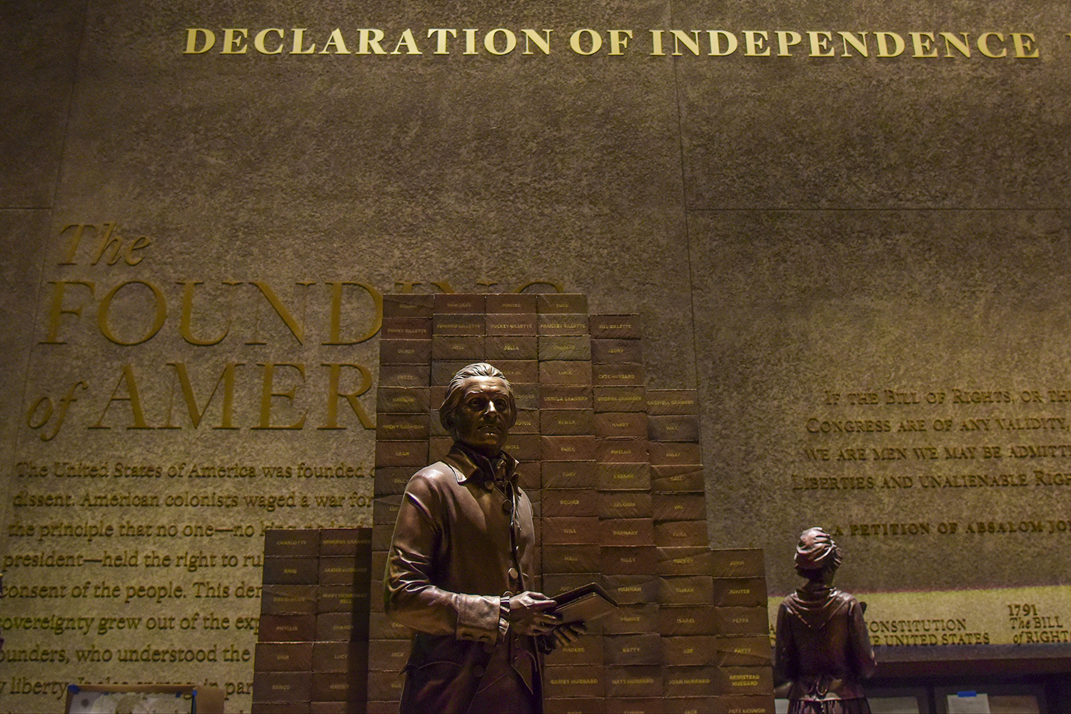 A statue of Thomas Jefferson stands next to a stack of bricks marked with the names of people he enslaved—all under the words of the Declaration of Independence—at the Smithsonian In-stitution's National Museum of African American History and Culture in Washington on Sept. 14, 2016.