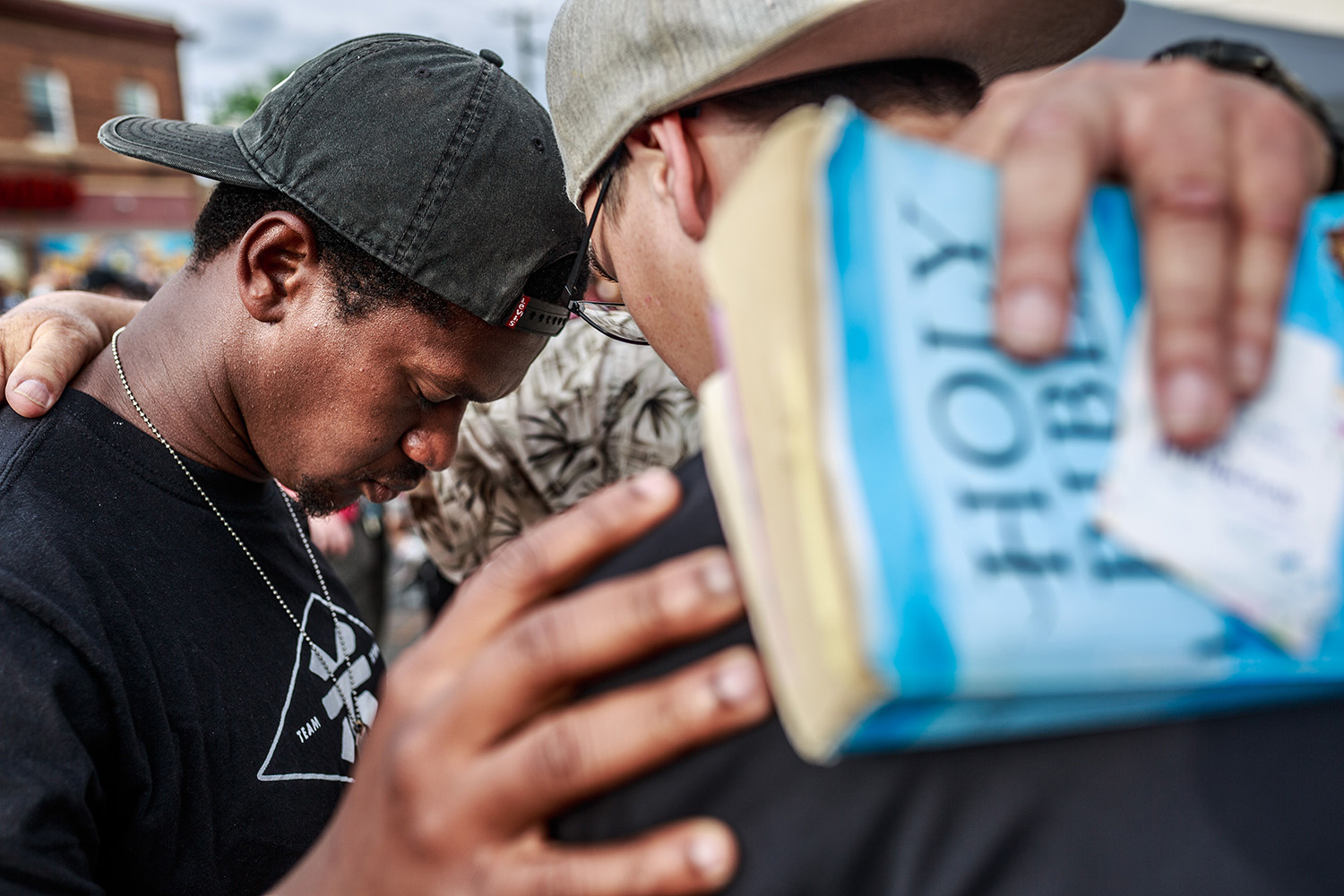 Men pray during a Juneteenth ceremony near the site where George Floyd died in police custody in Minneapolis, Minnesota, on June 19. KEREM YUCEL/AFP via Getty Images