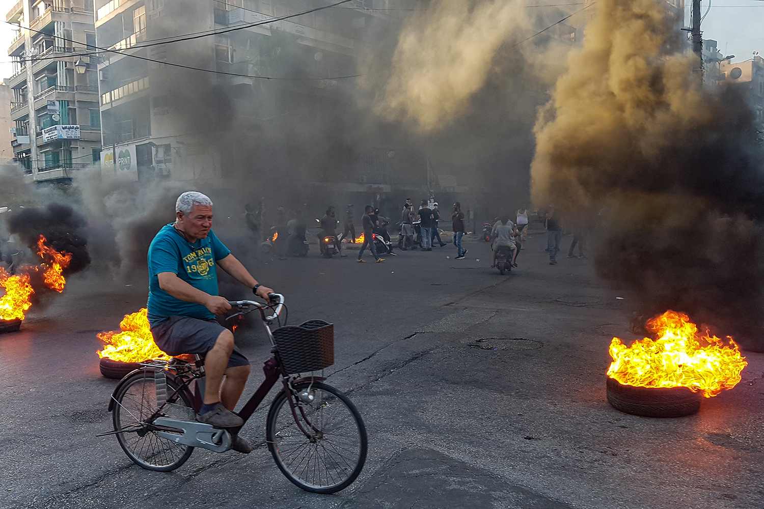 A man cycles past tires set aflame by protesters in Lebanon's northern city of Tripoli on June 11 as people take to the streets to demonstrate against dire economic conditions. FATHI AL-MASRI/AFP via Getty Images