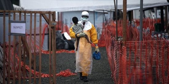 A Doctors Without Borders health worker carries a child suspected of having Ebola in Paynesville, Liberia, on Oct. 5, 2014.