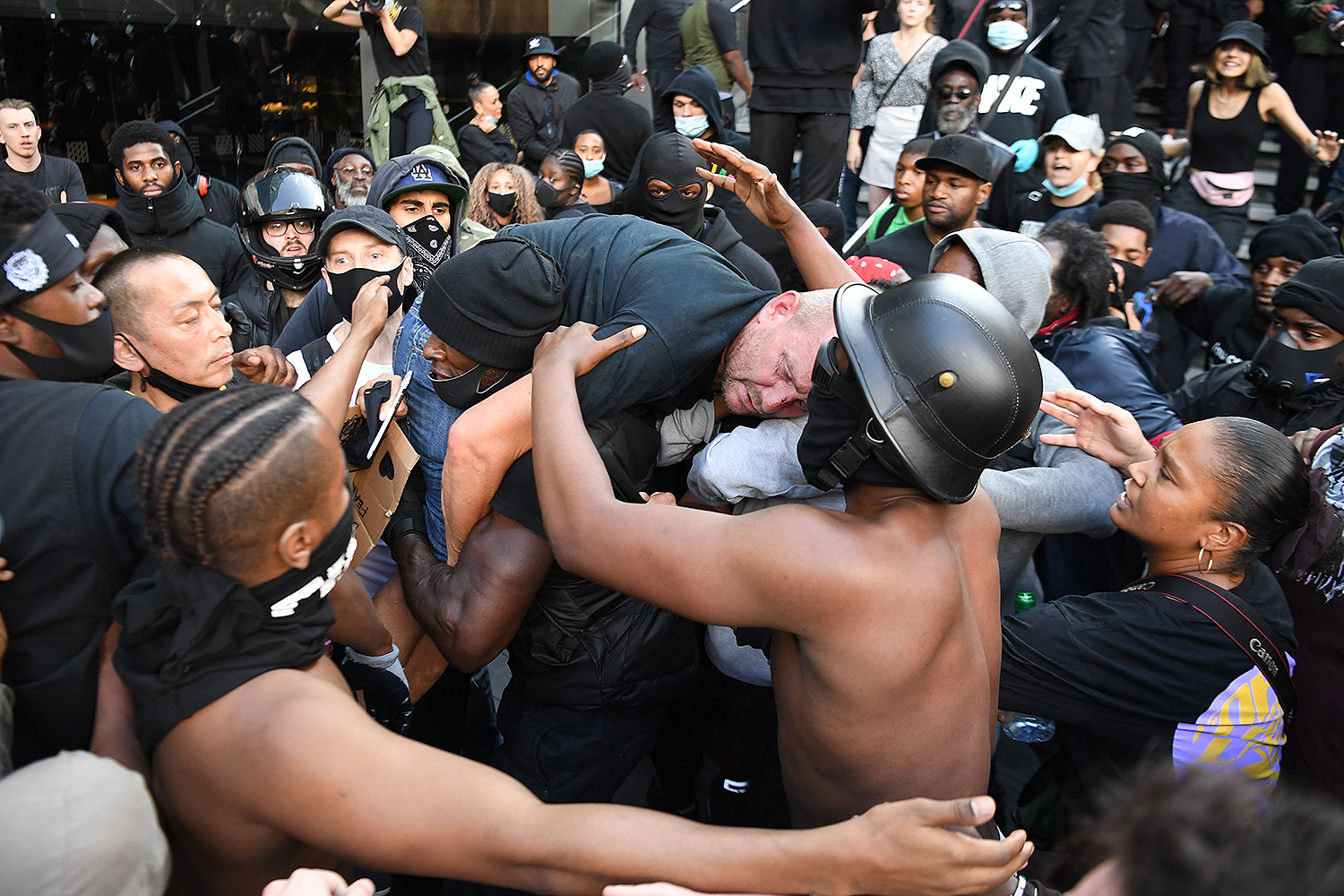 A man is carried to police lines after being beaten in clashes between protesters supporting the Black Lives Matter movement and far-right activists in London on June 13. DANIEL LEAL-OLIVAS/AFP via Getty Images
