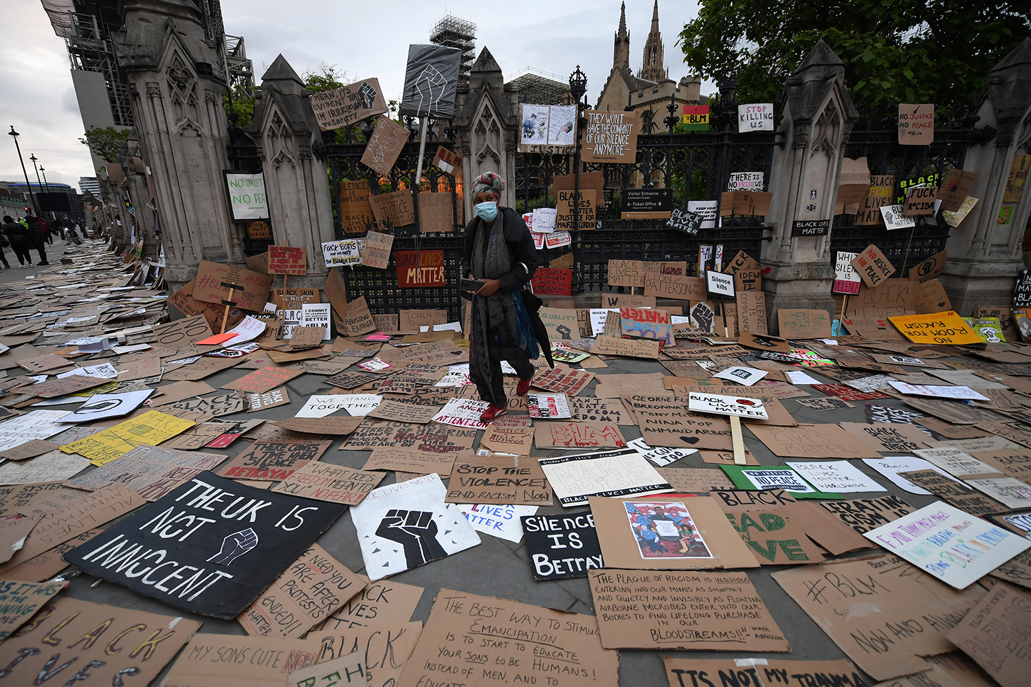 A woman walks among placards and signs left outside the Houses of Parliament during a Black Lives Matter protest in Westminster, London, on June 7. Chris J Ratcliffe/Getty Images