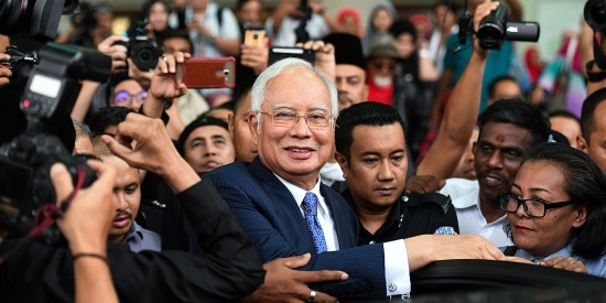 Malaysia's former prime minister Najib Razak (center) leaves a court in Kuala Lumpur on April 3, 2019, while on trial for alleged involvement in the looting of the 1MDB sovereign wealth fund.