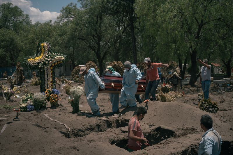 Workers carry a casket to its burial site as a family member (far right) records the moment on his phone at the San Lorenzo Tezonco public cemetery in Iztapalapa, Mexico City, on May 19.