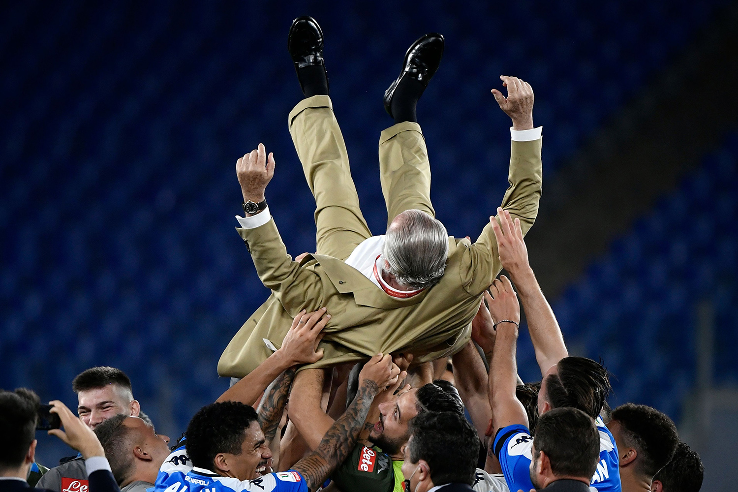 Players throw Napoli president Aurelio De Laurentiis in the air as they celebrate their Italian Cup win at the Olympic Stadium in Rome on June 17. It was the Naples football team's first trophy in six years. FILIPPO MONTEFORTE/AFP via Getty Images