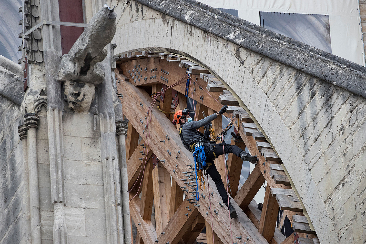 A man works on a wooden consolidation of a flying buttress at Notre Dame Cathedral in Paris on June 9 as crews begin the delicate task of removing tons of metal scaffolding that melted together during last year's fire—one of the riskiest operations in the rebuilding effort so far. THOMAS SAMSON/AFP via Getty Images