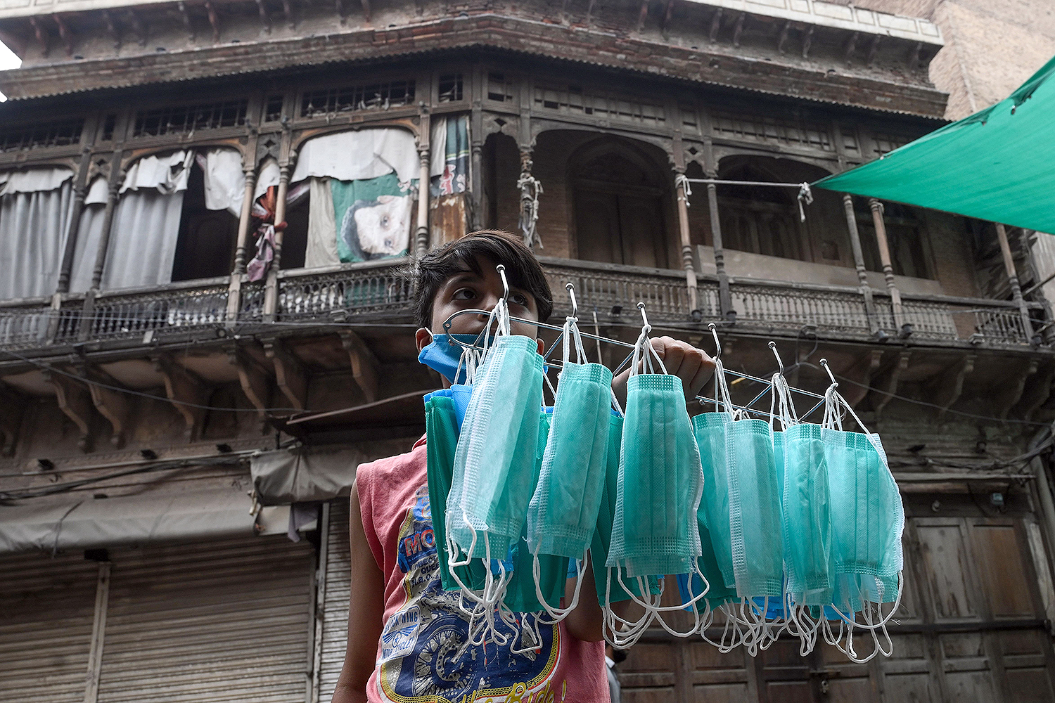 A young vendor sells face masks on a street in Lahore, Pakistan, on June 25 as coronavirus cases continue to rise. ARIF ALI/AFP via Getty Images