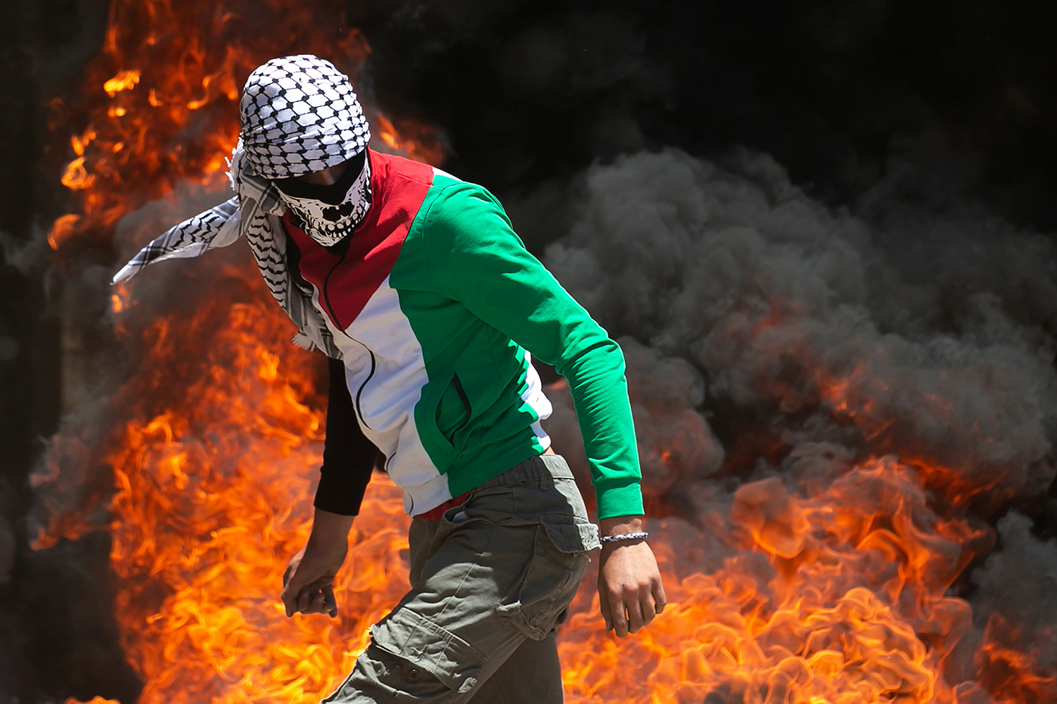A Palestinian protester walks near burning tires during clashes with Israeli forces in the village of Kafr Qaddum, in the Israeli-occupied West Bank, on June 12. Protests were sparked by the Jewish state's plans to annex part of the territory. JAAFAR ASHTIYEH/AFP via Getty Images