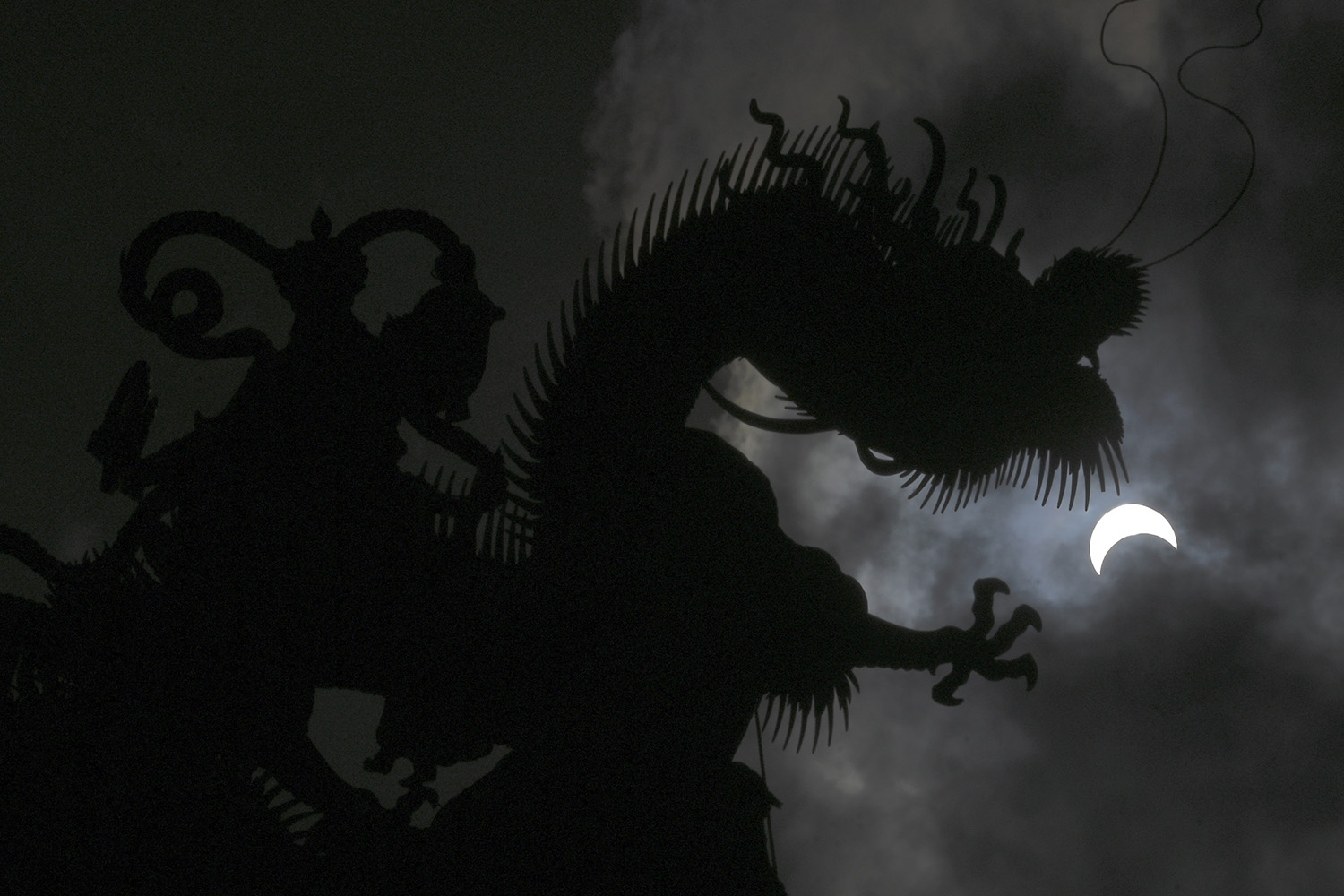 A partial eclipse is seen next to a dragon statue at a Taoist temple in Yunlin County, Taiwan, on June 21. SAM YEH/AFP via Getty Images