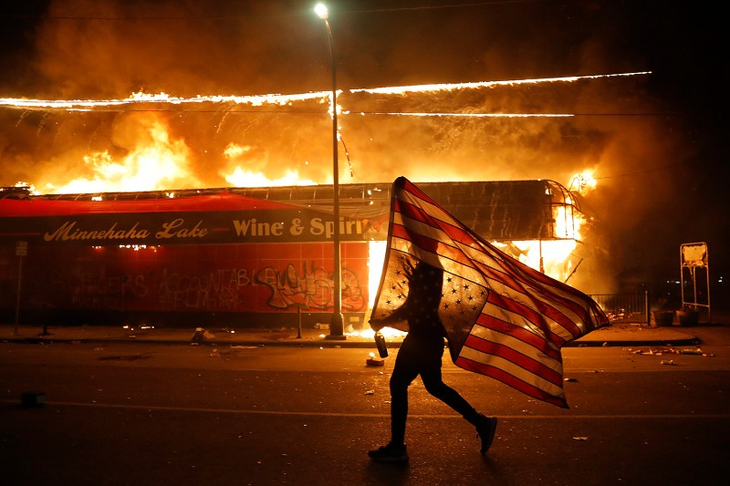 A protester carries an upside-down U.S. flag, a sign of distress, next to a burning building in Minneapolis on May 28. Protests broke out all across the nation—and in many other countries, including New Zealand, France, and Spain—over the death of George Floyd, a black man who died in Minneapolis police custody three days earlier. Julio Cortez/The Associated Press