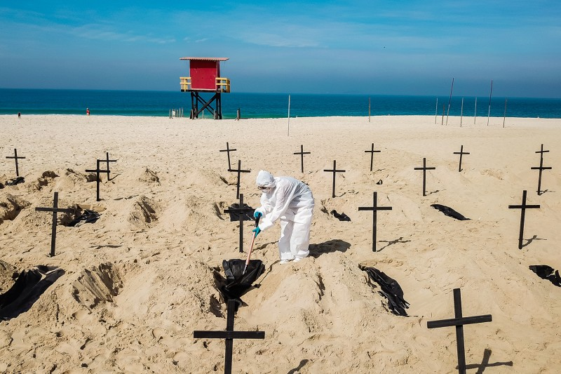 Protesters dig symbolic graves at Rio de Janeiro's Copacabana Beach on June 11, calling for transparency and change in the way the government is fighting the coronavirus pandemic, which has killed more than 40,000 in Brazil. Buda Mendes/Getty Images