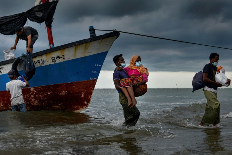 Acehnese fishermen help evacuate a Rohingya woman onto the shorelines of Lancok village in Indonesia's North Aceh Regency on June 25. Nearly 100 Rohingya from Myanmar, including 30 children, were rescued from a rickety wooden boat off the coast of Sumatra island, a maritime official said. CHAIDEER MAHYUDDIN/AFP via Getty Images