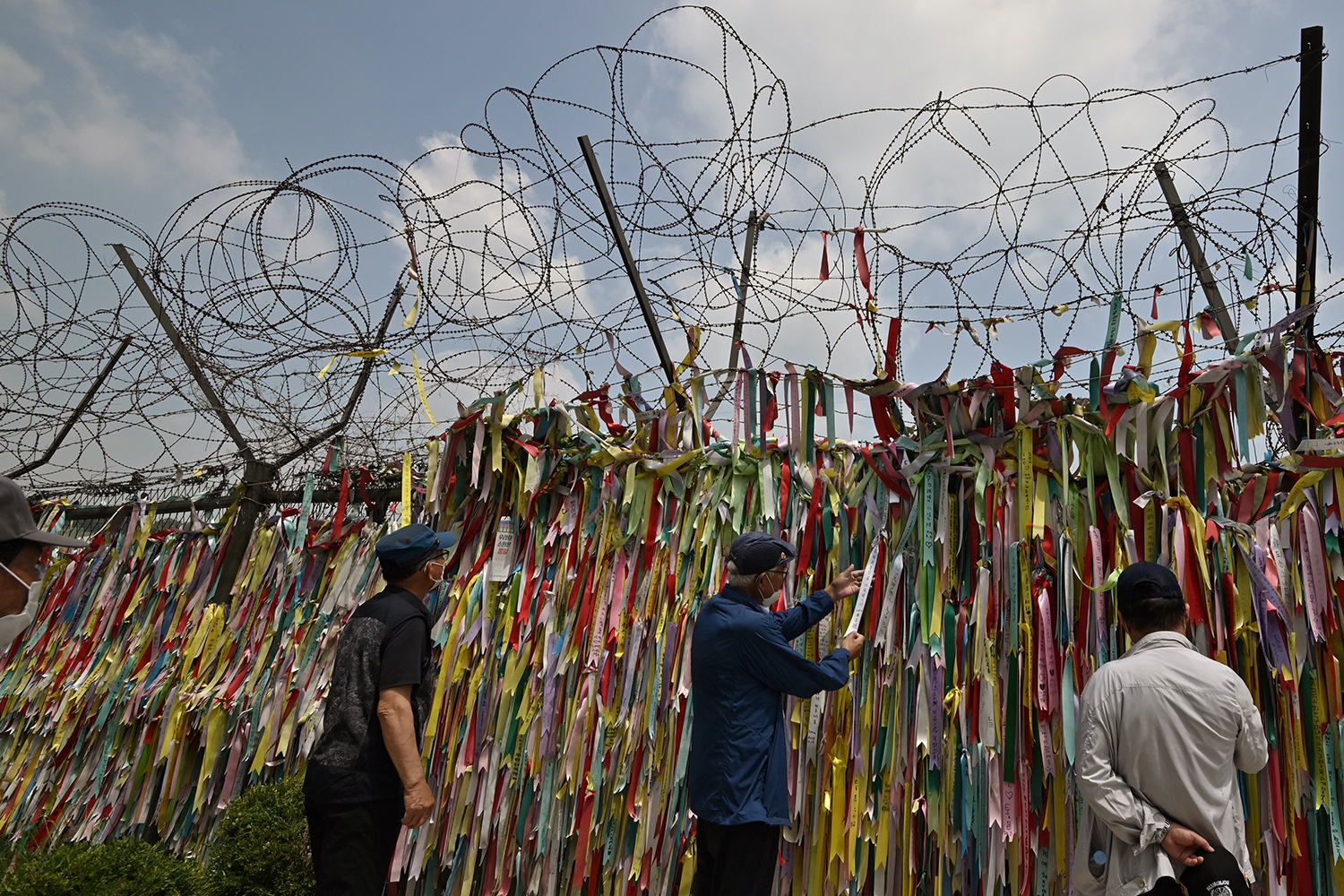 Visitors look at ribbons wishing for peace and reunification of the Korean Peninsula on a military fence in the border city of Paju, South Korea, on June 16. JUNG YEON-JE/AFP via Getty Images