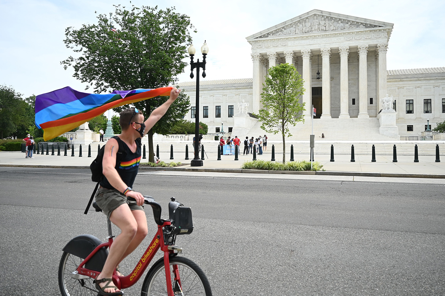 A man waves a rainbow flag as he rides by the U.S. Supreme Court in Washington on June 15 after its decision to protect LGBTQ workers from workplace discrimination. JIM WATSON/AFP via Getty Images