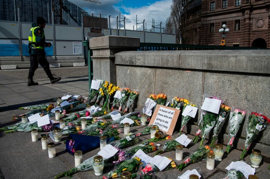 A memorial to coronavirus victims is set up in Stockholm's Mynttorget square April 29, featuring candles, flowers, and handwritten notes, some of which express frustration over Sweden's softer approach to handling the pandemic.