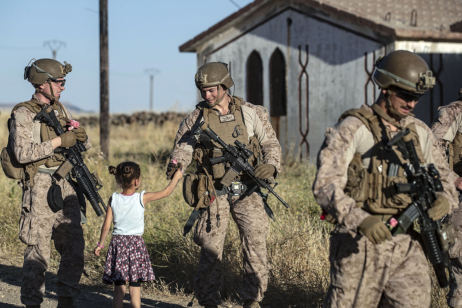 A Syrian girl gives flowers to U.S. soldiers as their convoy makes a stop in the northeastern Syrian town of al-Malikiyah (known to Kurds as Derik) during a patrol of Kurdish towns near the border with Turkey on June 7. DELIL SOULEIMAN/AFP via Getty Images