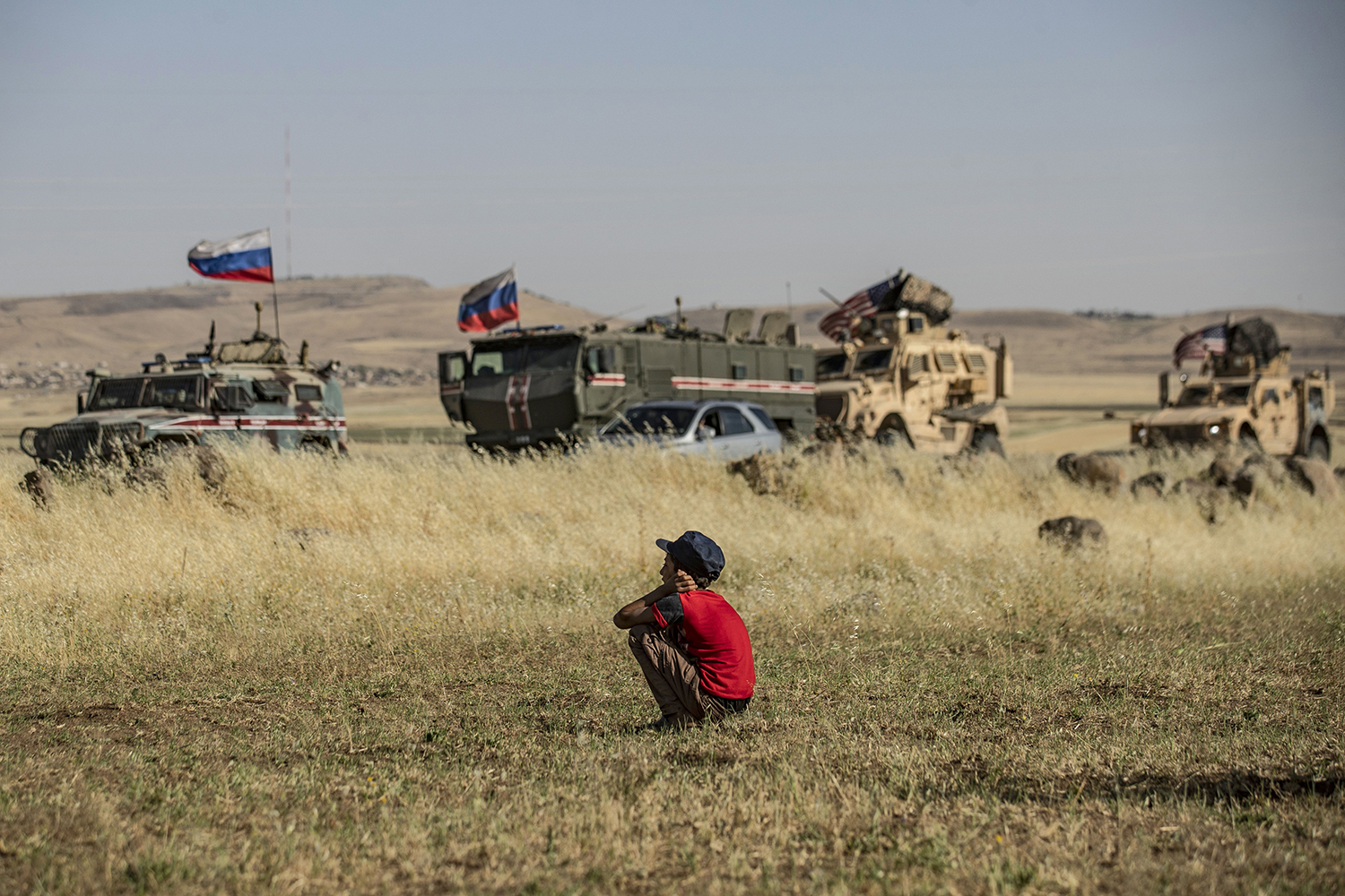 A Syrian boy looks at Russian and U.S. military vehicles in the northeastern Syrian town of al-Malikiyah at the border with Turkey on June 3. DELIL SOULEIMAN/AFP via Getty Images