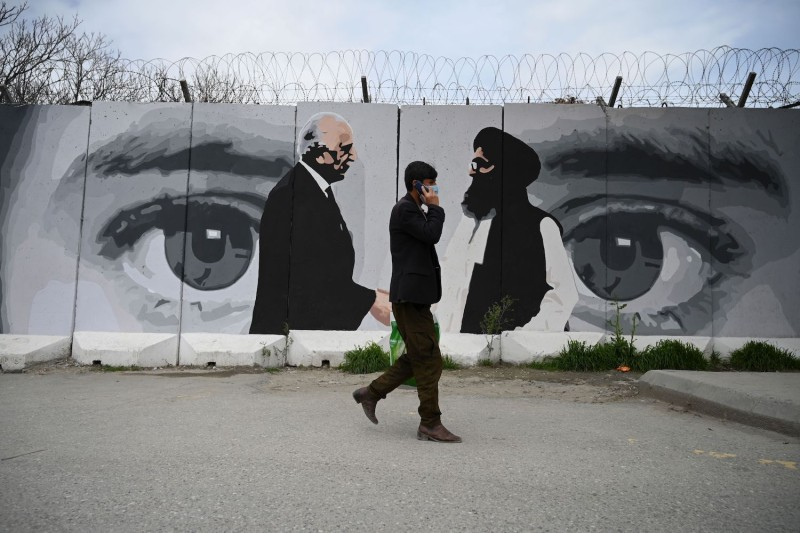A man walks past a wall painted with images of US Special Representative for Afghanistan Reconciliation Zalmay Khalilzad and Taliban co-founder Mullah Abdul Ghani Baradar, in Kabul April 5, 2020.