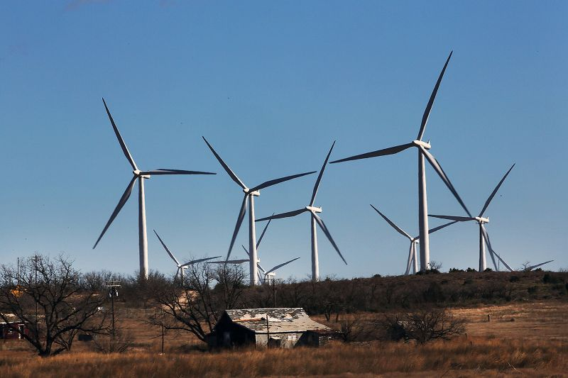 Wind turbines tower over a building on a farm in Colorado City, Texas, on Jan. 21, 2016.