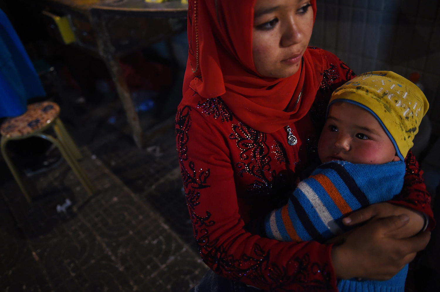 A Uighur woman holds her baby at a night market in Hotan, in China's western Xinjiang region on April 15, 2015.