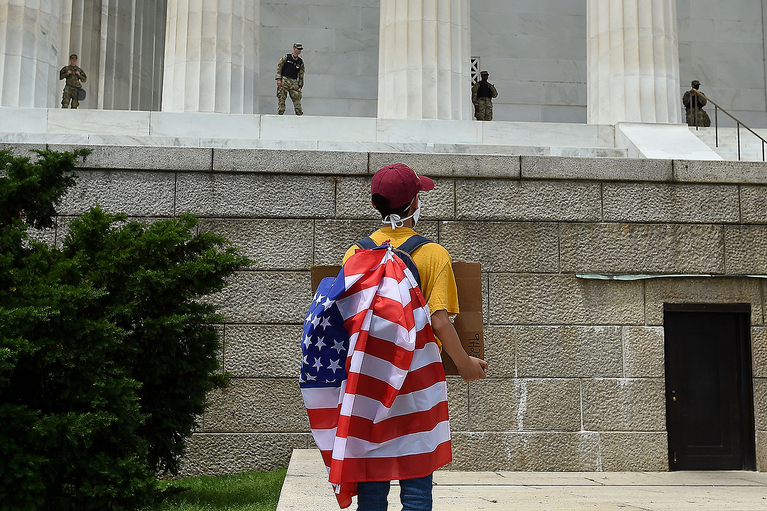 A protester faces National Guard members standing watch at the Lincoln Memorial in Washington, D.C., on June 6 during a protest against police brutality and racism. OLIVIER DOULIERY/AFP via Getty Images