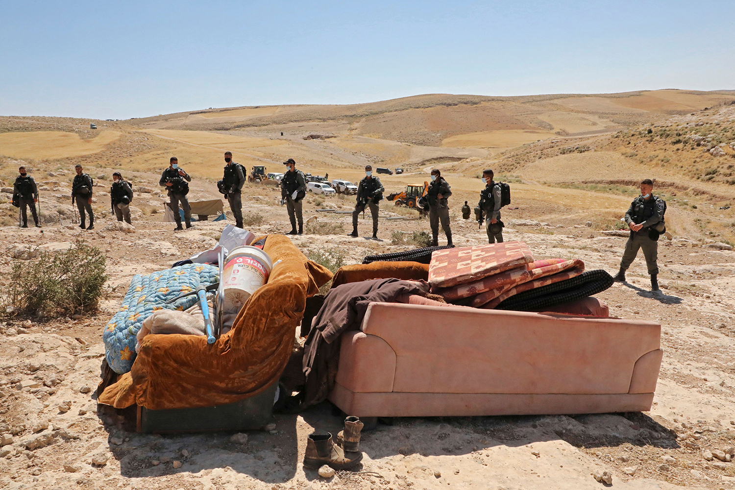 Israeli forces stand by furniture after structures used as homes by Palestinians were demolished south of Yatta village in the southern West Bank district of Hebron on June 3 following an order issued by Israeli authorities. HAZEM BADER/AFP via Getty Images