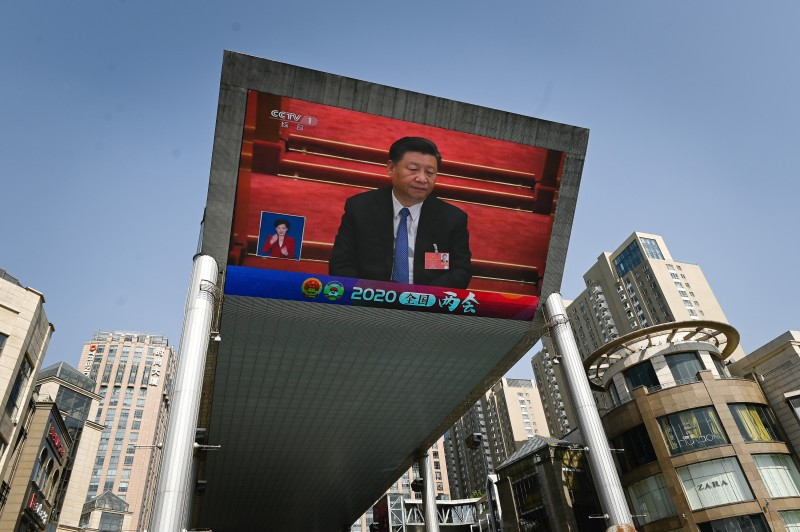 An outdoor screen shows live coverage of Chinese President Xi Jinping attending the closing session of the National People's Congress in Beijing on May 28. WANG ZHAO/AFP via Getty Images