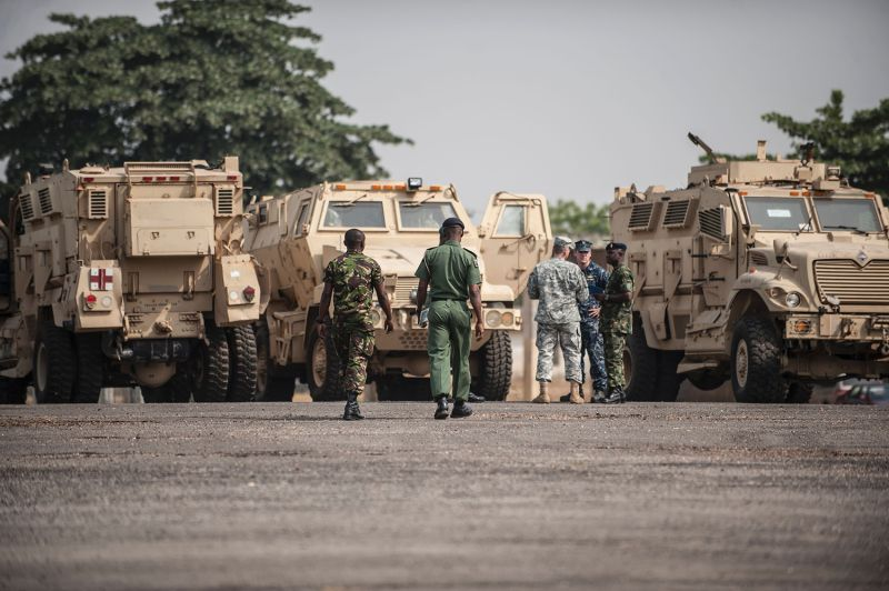 Members of the Nigerian and U.S. military stand next to some of the 24 armored vehicles donated to the Nigerian government in Lagos on Jan. 7, 2016.