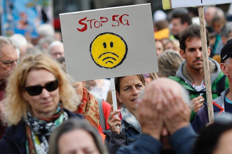 A demonstrator holds a placard reading 'Stop 5G', during a protest against the 5G (fifth generation) mobile communications network in Bern on May 10, 2019.
